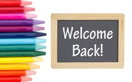 Welcome Back message on a chalkboard with colored watercolor pencils stock photo