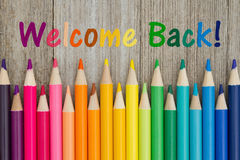 Welcome back message. Welcome back text with colorful pencil crayons on a weathered wood royalty free stock image