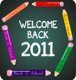 Welcome back to school 2011. Blackboard with chalk writing and colored pencils royalty free illustration