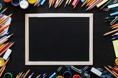 Welcome back to school background with kids supplies for modern primary education, color pencils, paints and frame on dark black stock images