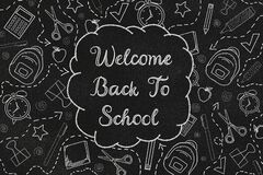 Welcome back to school with doodles on a black chalkboard. Textured background.