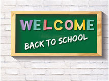 Welcome back to school green chalkboard. Welcome back to school sign on a green chalkboard with a brick background Royalty Free Stock Photos