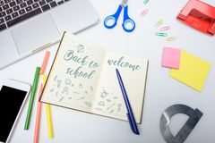 Welcome back to school. Lettering welcome back to school in notebook, digital devices and school equipment royalty free stock image
