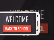 Welcome back to school written on blackboard with cellphone Royalty Free Stock Photos