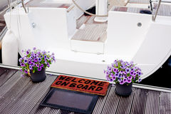 Welcome on board. A welcome on board doormat and flowers at the entry to a yacht Royalty Free Stock Photos