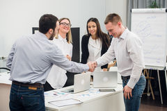 Welcome on board. Four business people sitting at the table while two of them shaking hands and smiling Stock Photos