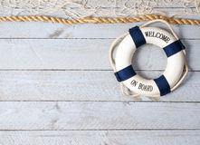 Welcome on board. Life preserver with welcome on board in text with white fishing net and rope against weathered white boards stock photos