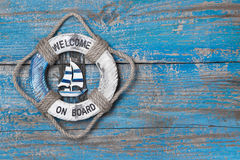 Welcome on board. Lifebuoy blue wooden background