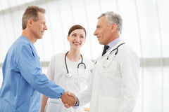 Welcome on board! Two mature doctors handshaking while  beautifu Royalty Free Stock Images