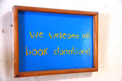 Welcome Book Donations Sign. A handmade wooden and painted sign stating We Welcome All Book Donations Royalty Free Stock Photography