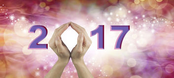 Welcome 2017 with both hands. Female using both hands to make an O in the year number 2017 on a warm red and pink colored starry bokeh background stock photos