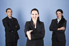 Welcome business gesture. Business women giving welcome gesture in the middle of her colleagues on blue background,check also Business people Royalty Free Stock Photography