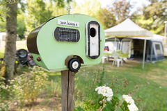 Welcome at the camping. Funny vintage caravan for welcome at the camping royalty free stock image