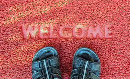 Welcome capet with foot ware on it. Royalty Free Stock Photography