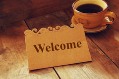 Welcome card over wooden table next to coffee cup Royalty Free Stock Image
