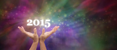 Welcome in 2015 Celebration Banner. Female hands outstretched facing upwards, with a white 2015 floating above on a deep rainbow colored sparkly flowing bokeh Royalty Free Stock Photography