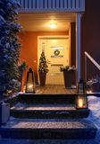 Welcome Christmas house entrance door in Xmas evening. Welcome Christmas - house entrance snowy steps and door with decoration stock photo