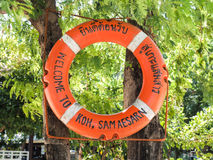 Welcome Circular red Life Buoy hanging on the tamarind tree Stock Image