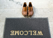 Welcome cleaning foot carpet with shoes Royalty Free Stock Photography