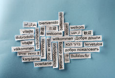 Welcome collage. Welcome Word Cloud printed on paper on blue font stock image