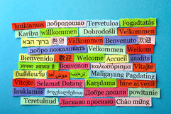Welcome collage. Welcome Word Cloud printed on paper on blue font royalty free stock image
