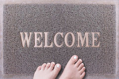 Welcome Door Mat With Female Feet. Friendly Grey Door Mat Closeup with Bare Woman Feet Standing. Welcome Carpet. Royalty Free Stock Photos