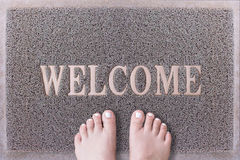 Welcome Door Mat With Female Feet. Friendly Grey Door Mat Closeup with Bare Woman Feet Standing. Welcome Carpet. Stock Images