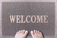 Welcome Door Mat With Female Feet. Friendly Grey Door Mat Closeup with Bare Woman Feet Standing. Welcome Carpet. Girl Feet with White Painted Toenails on Foot Stock Photo