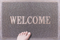 Welcome Door Mat With Female Foot. Friendly Grey Door Mat Closeup with Bare Woman Foot Standing. Welcome Carpet. Stock Images