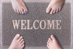 Welcome Door Mat With Funny Family Feet. Friendly Grey Door Mat Closeup with Four Bare Feet Standing. Four Feet on Stock Photography