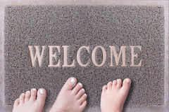 Welcome Door Mat With Three Feet. Friendly Grey Door Mat Closeup with Bare Feet Standing. Welcome Carpet. Three Feet on Foot Scraper Royalty Free Stock Image