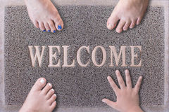 Welcome Door Mat With Three Feet and One Hand. Stock Image