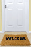 Welcome doormat outside a door. Royalty Free Stock Photography