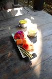 Welcome drink, fruit plate, Tropical resort. A photograph showing a bright sunny tropical resort wood table with two small white silver cups of cool pandan and Stock Photos