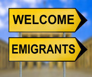 Welcome and Emigrants traffic sign with blurred Berlin backgroun Royalty Free Stock Image