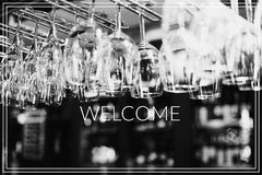 Welcome. Empty glasses for wine above a bar rack Royalty Free Stock Photos