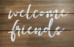 Welcome friends sign. White welcome friends sign print on wood wall Stock Photos