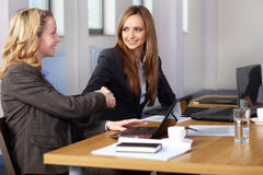 Welcome handshake before business meeting. Young blonde and brunette businesswomen sitting at conference table Royalty Free Stock Images