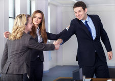 Welcome handshake before business meeting. Businesswomen introduce two colleagues, welcome handshake before business meeting Royalty Free Stock Image