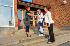 Welcome handshake between schoolgirl mother and teacher Stock Images