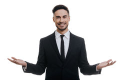 Welcome!. Handsome young man in full suit looking at camera and keeping arms outstretched while standing against white background Stock Image