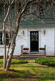 Welcome Home. Inviting home with spring flowers on the front porch. The magnolia tree in the front yard is in focus with the modest, well-manicured home in the stock photos