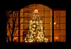Welcome Home Christmas Tree in Window. A brightly decorated Christmas tree in a window at night royalty free stock photos