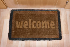 Welcome home doormat with closed door Royalty Free Stock Image