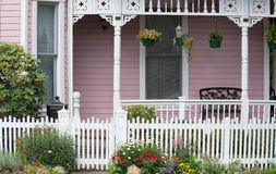 Welcome Home. The entrance to an old Victorian home behind a white wooden gate flanked by daisies, red coneflowers, violas, astilbes, and yellow pansies Royalty Free Stock Photo