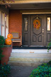 Welcome Home in Fall. Pair of pumpkins carved for Halloween sitting on steps of a brick house Royalty Free Stock Images