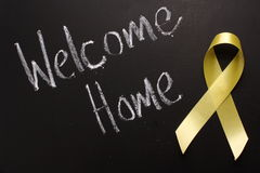 Welcome Home. The words Welcome Home written on a blackboard next to a traditional yellow ribbon Stock Photos