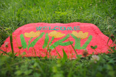 Welcome Mat. Photo of a welcome mat in front of a green meadow Royalty Free Stock Photo