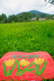 Welcome Mat. Photo of a welcome mat in front of a green meadow Royalty Free Stock Photography