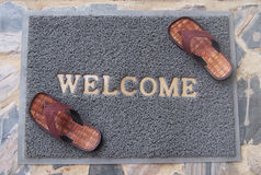 Welcome mat with brown sandals Stock Photos